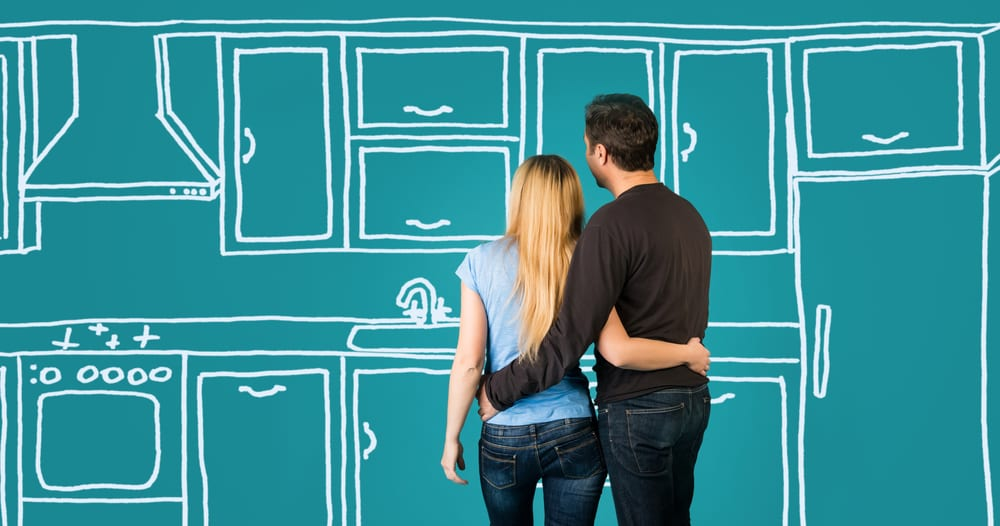 Couple embracing in front of kitchen sketch while planning kitchen renovation costs